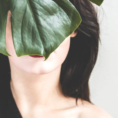 image of a brunette with a leaf in front of her face.
