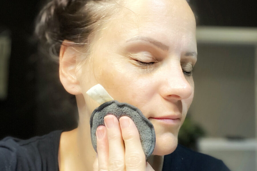 image of woman washing her face with a cleansing sponge